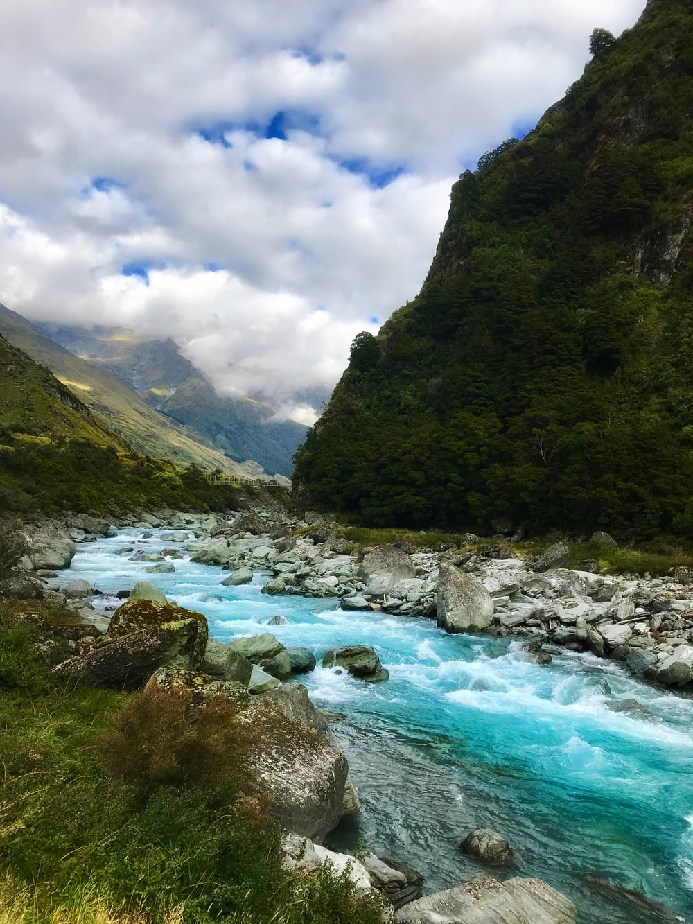 flowing river near green mountain under white clouds