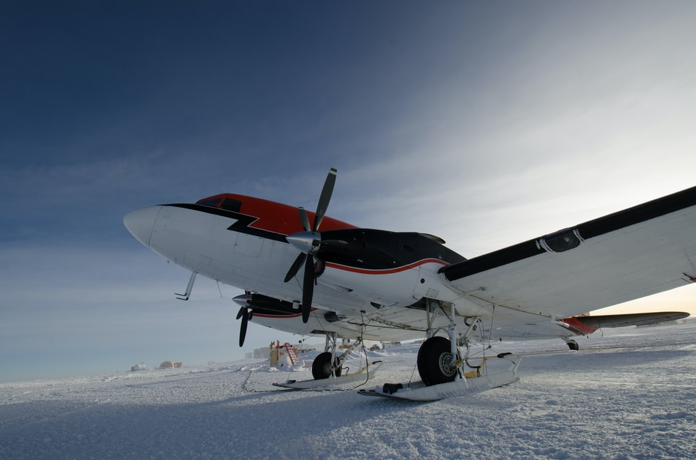 white, black, and red propeller plane on snow