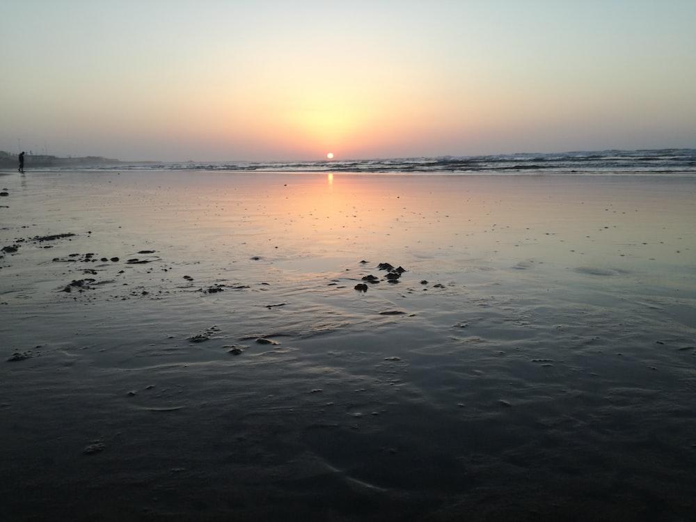 body of water across horizon during sunset