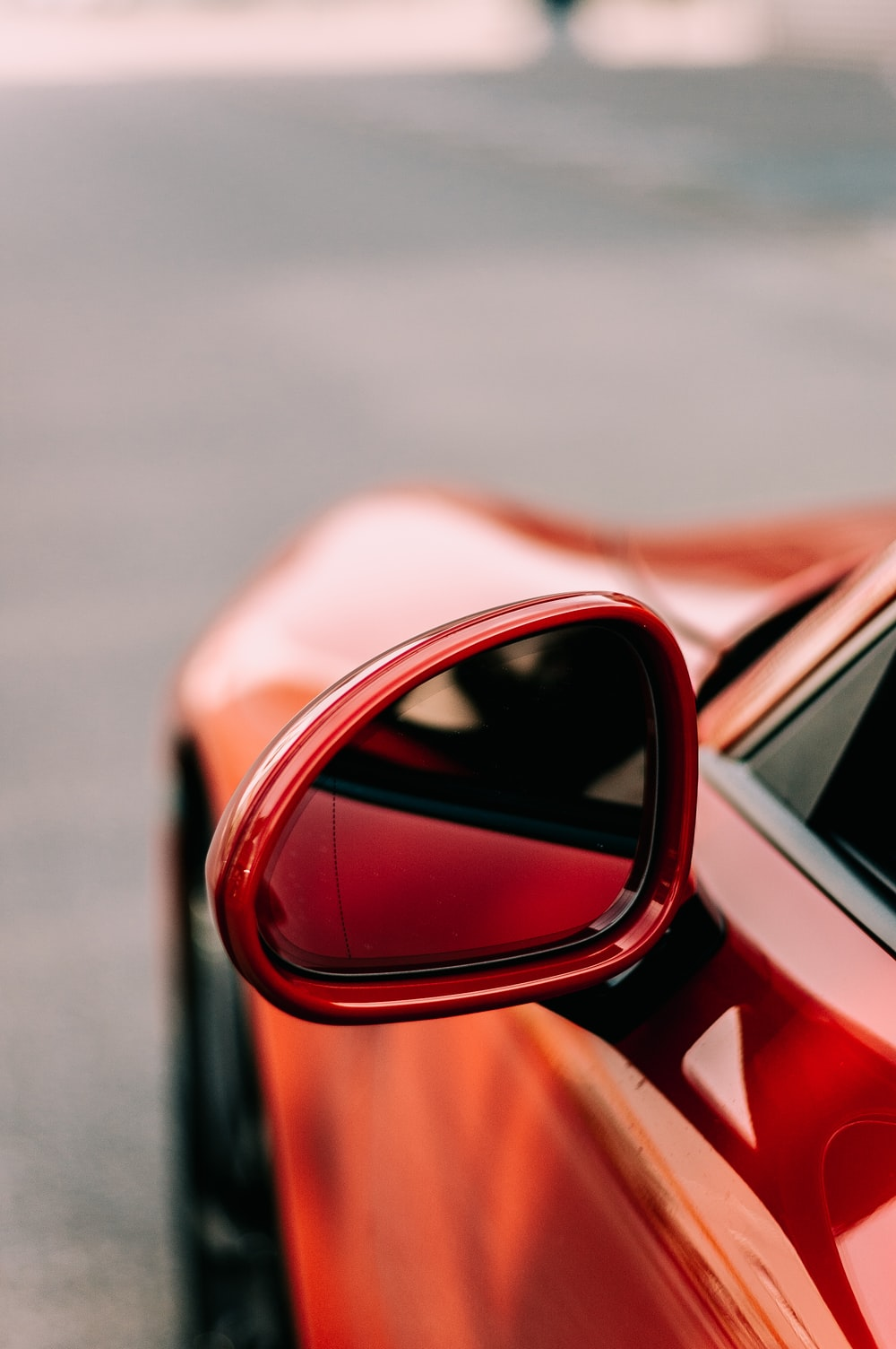 close-up photo of red vehicle wing mirror