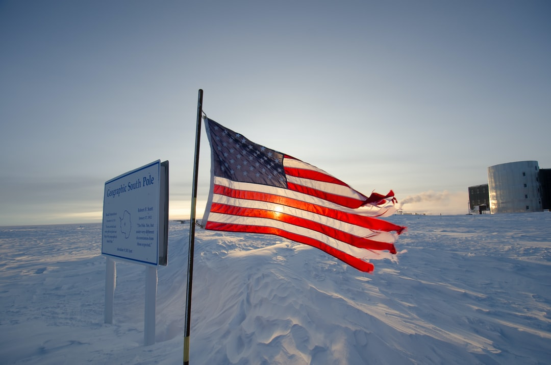The sun has risen. Four days after the austral vernal equinox. A wind-tattered American flag at South Pole Station is illuminated by a newly risen sun.