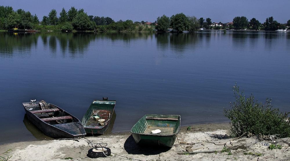three motor boats near seashore viewing lake
