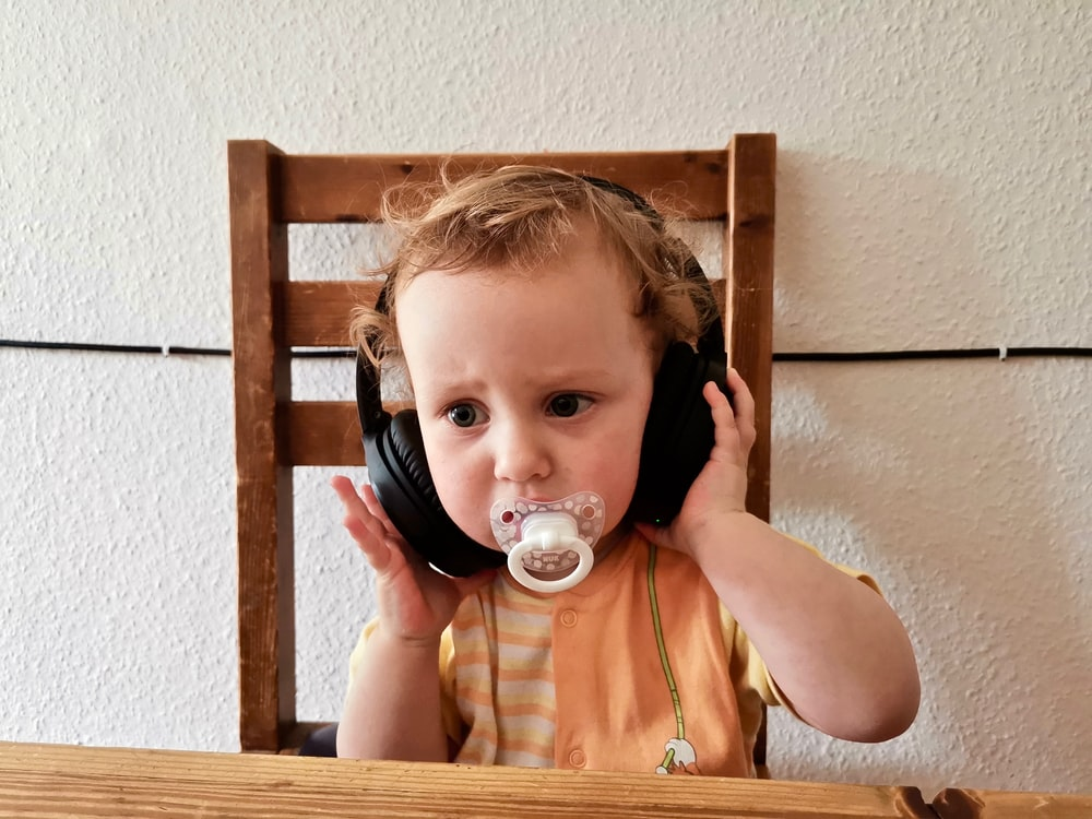 child with white pacifier using headphones while sitting on brown chair near table