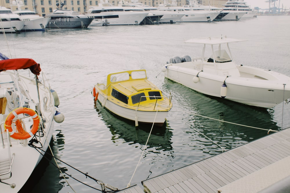 white yacht near white and yellow yacht beside dock
