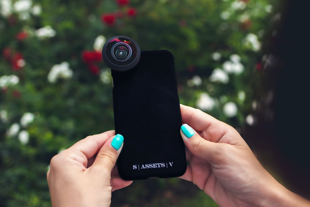 black smart phone with clip-on zoom lens