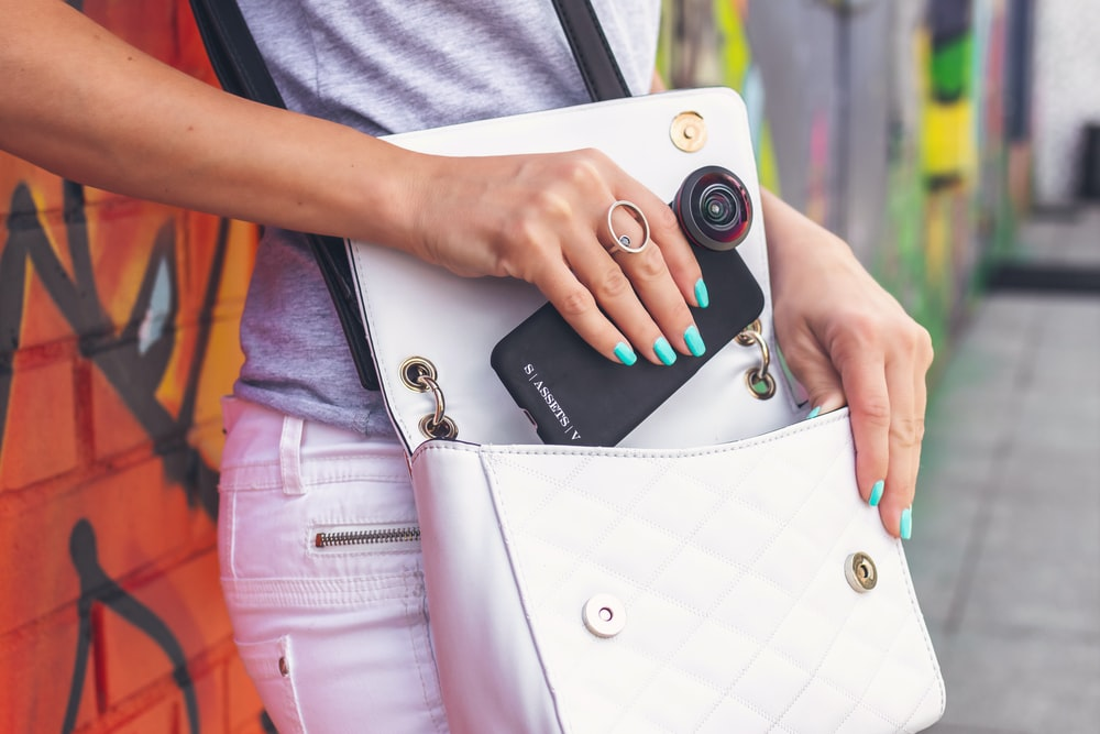woman taking out black smartphone from white leather crossbody bag