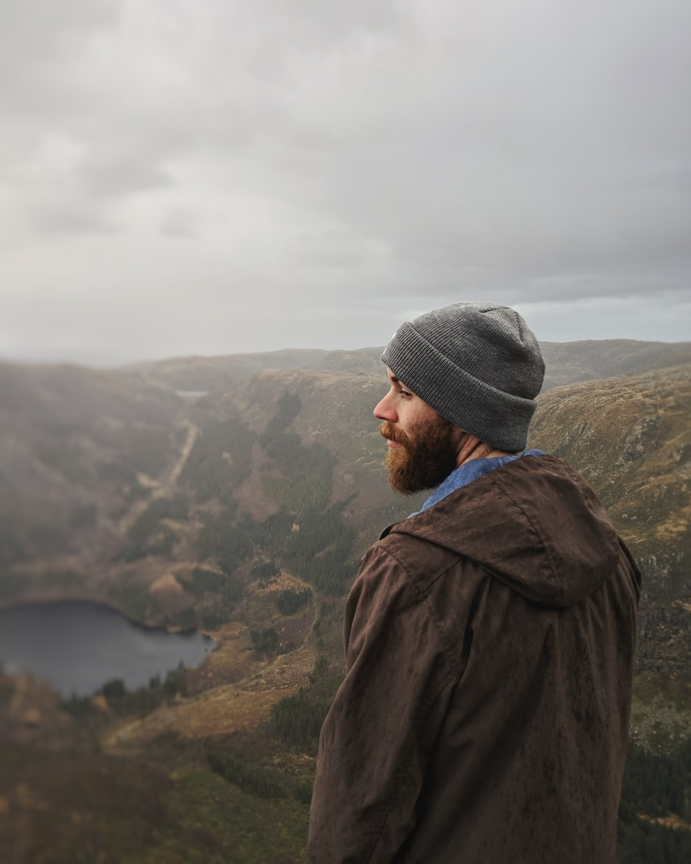 man standing and facing on lake and mountain