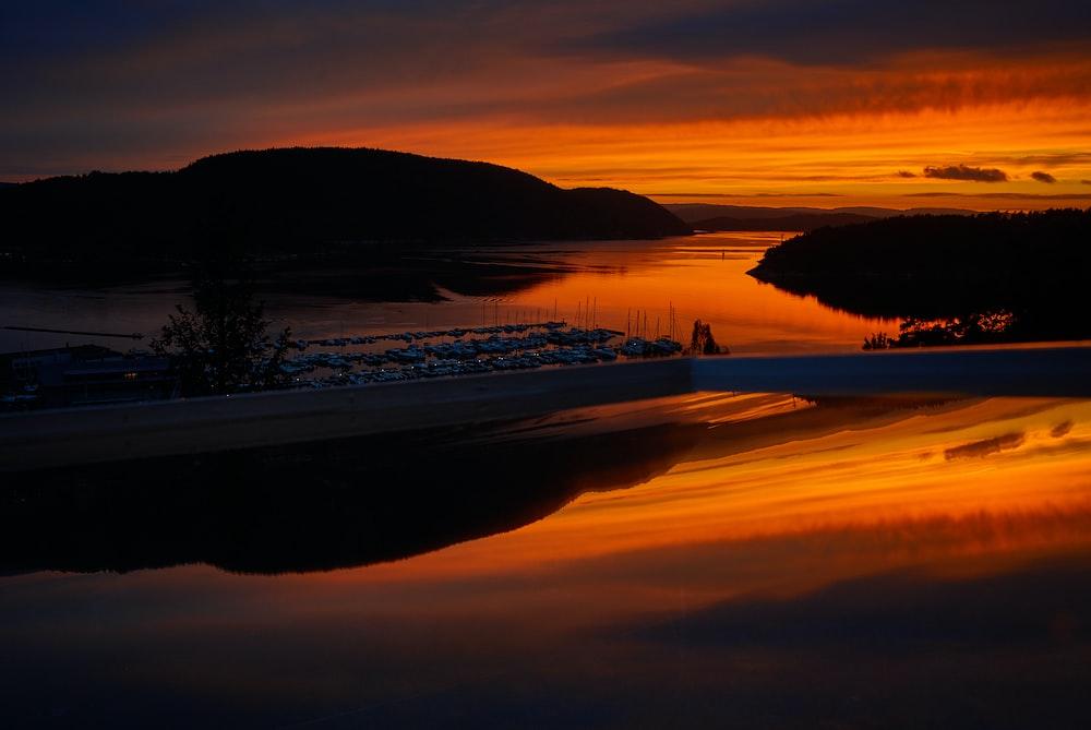 orange sky over boats moored in dock at sunset