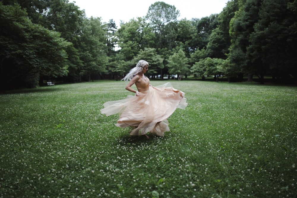 woman standing and dancing on green field