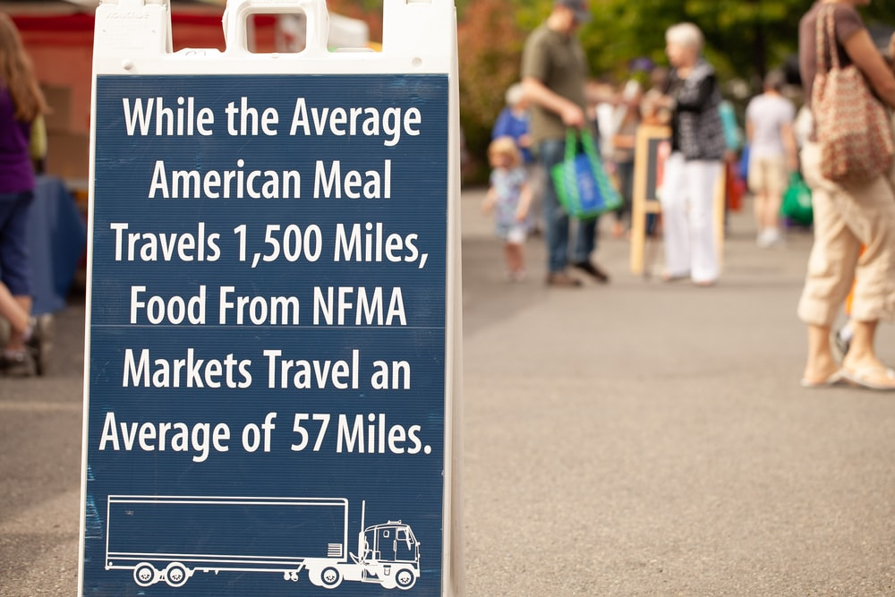 people standing near road with road sign saying while the average American meal travels 1,500 miles, food from NFMA markets travel an average of 57 miles