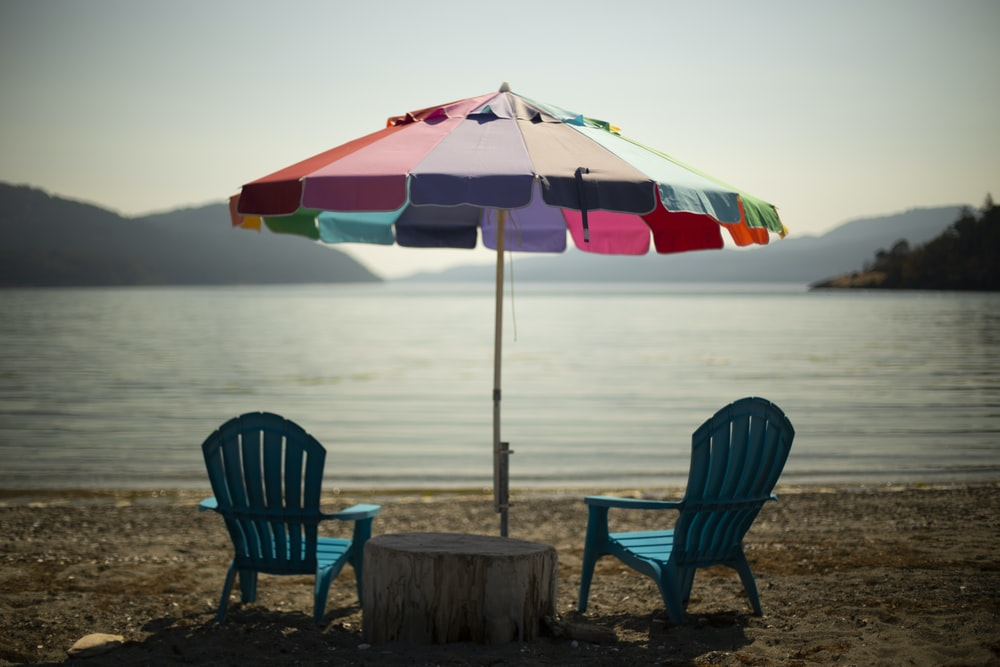 two blue lounge chairs under multicolored parasol in beach