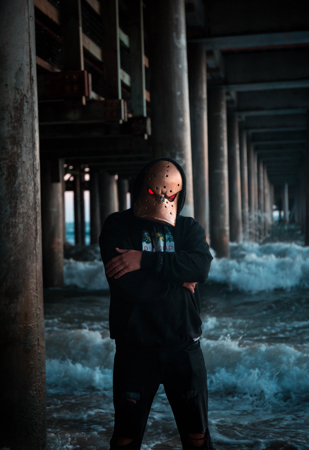 man wearing mask while standing under a bridge in the sea