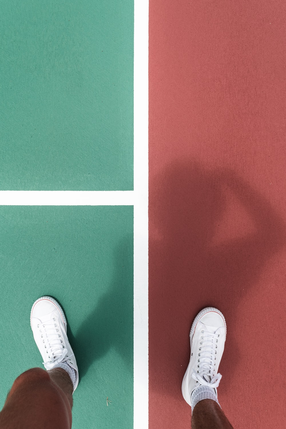 person wearing white sneakers standing on between green and red pavement