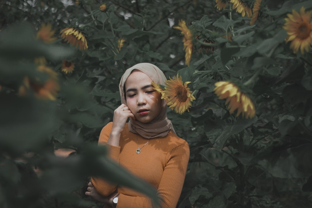 selective focus photography of woman surrounded with sunflowers
