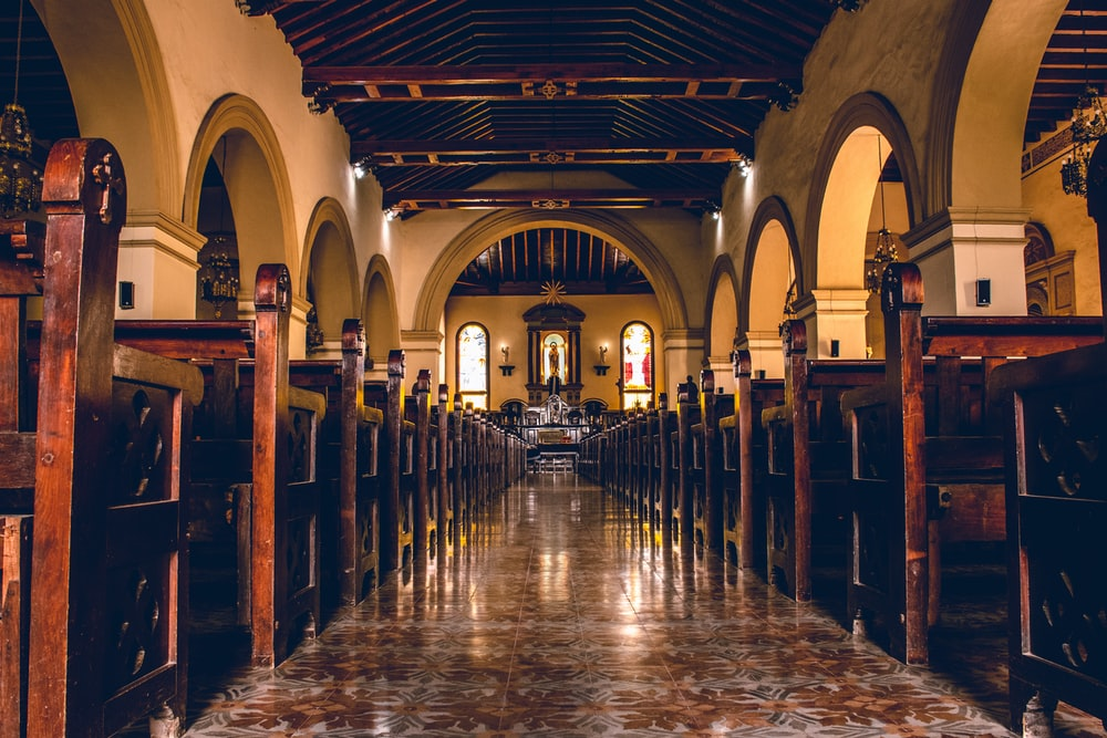 brown tiled aisle between benches inside church