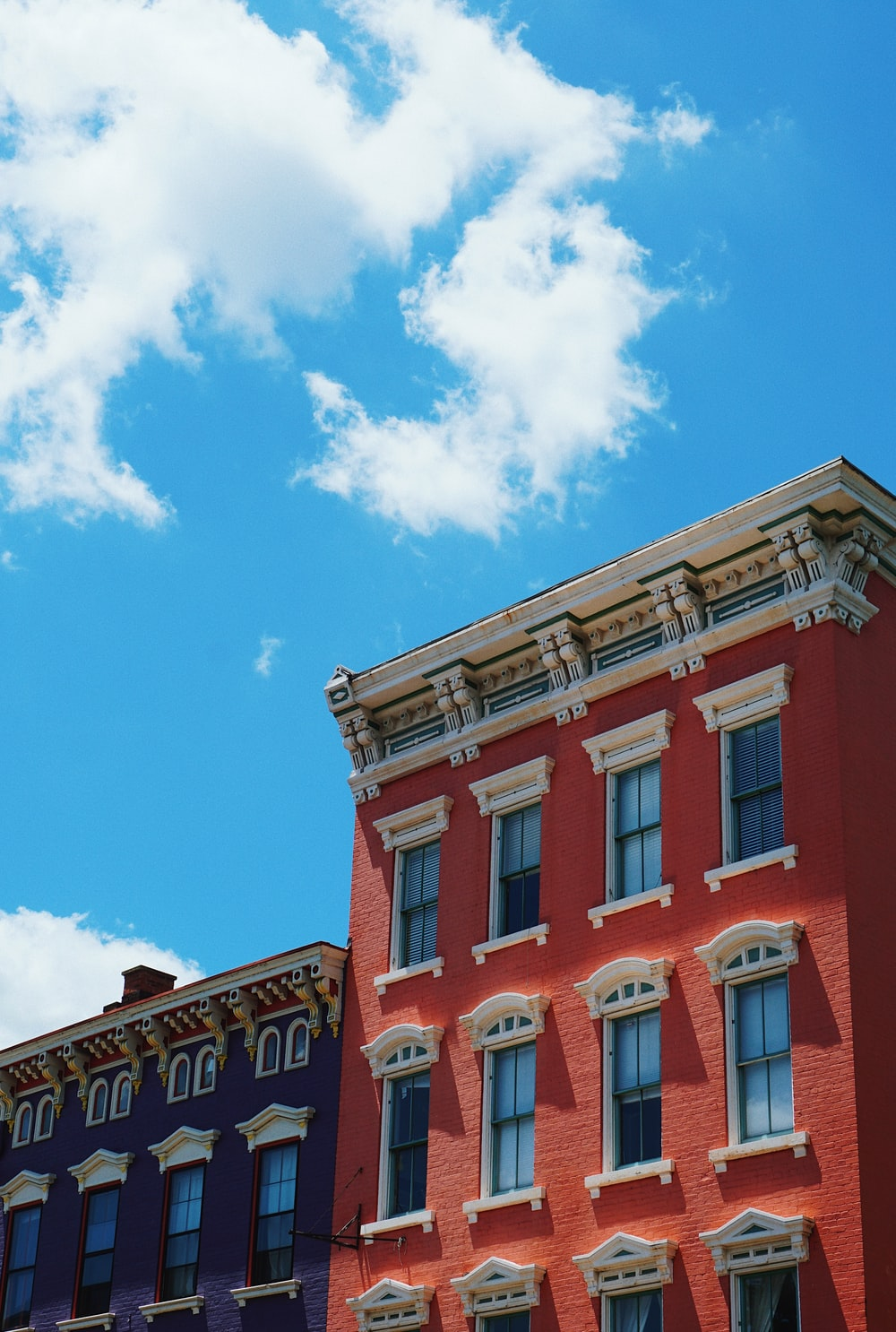 red and white apartment building across blue sky