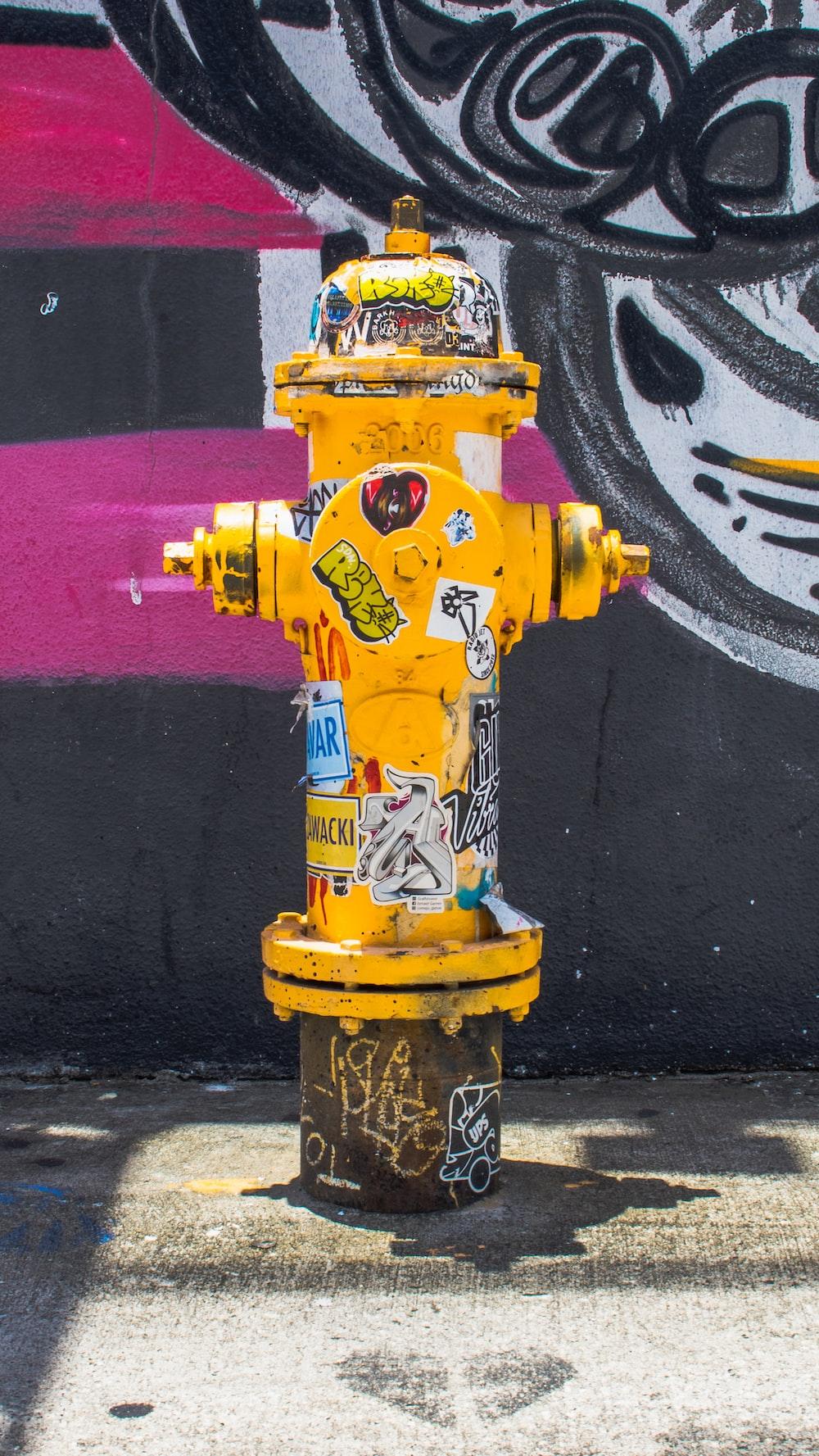 yellow fire hydrant near wall