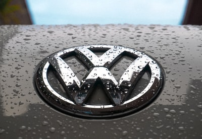 water dew on silver volkswagen car emblem volkswagen teams background