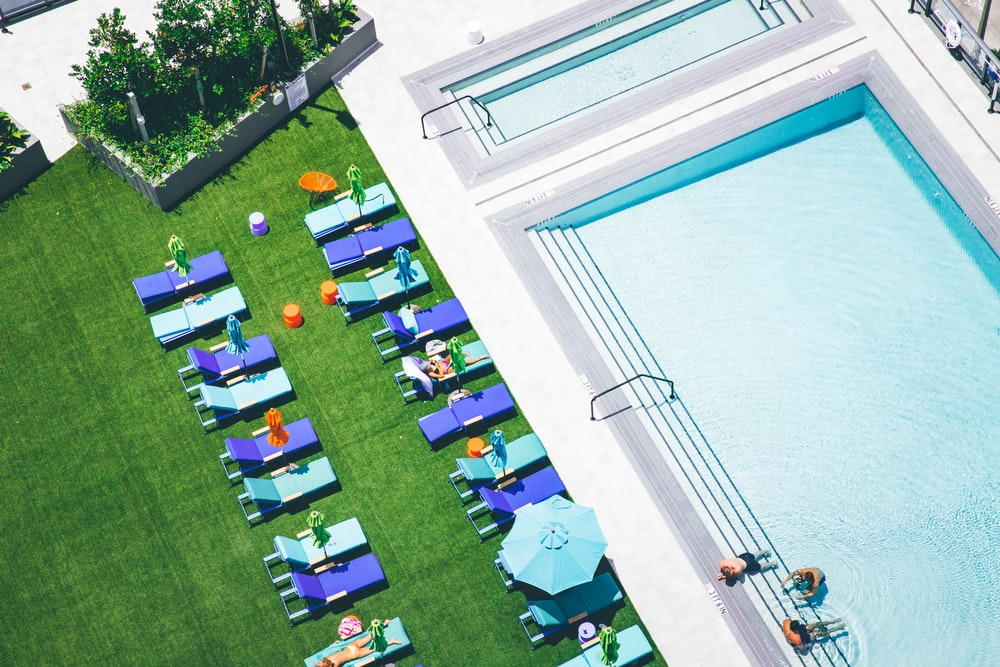 aerial photo of sunlounger near water pool