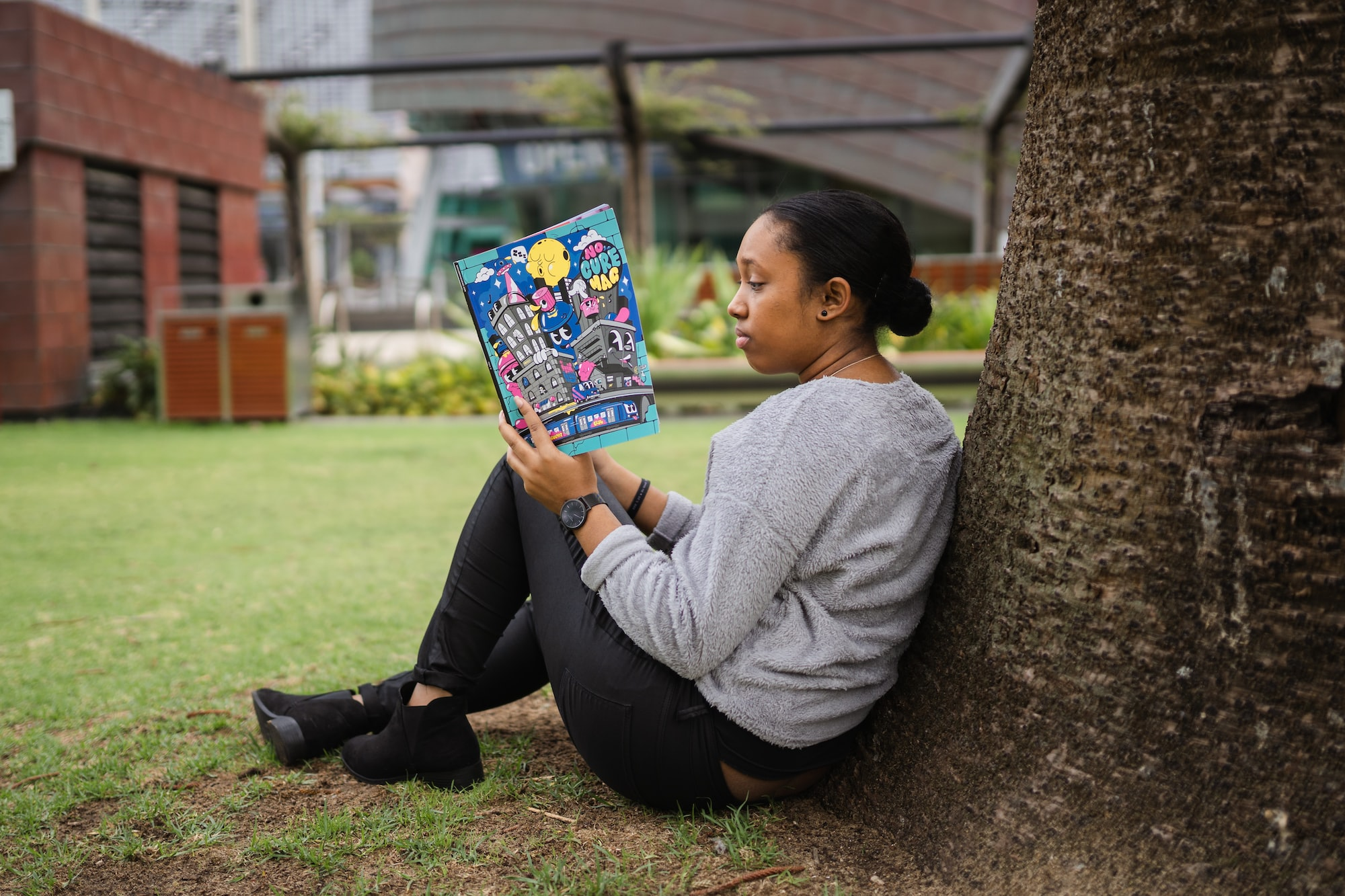 Young woman reading a magazine in the park, Perth.