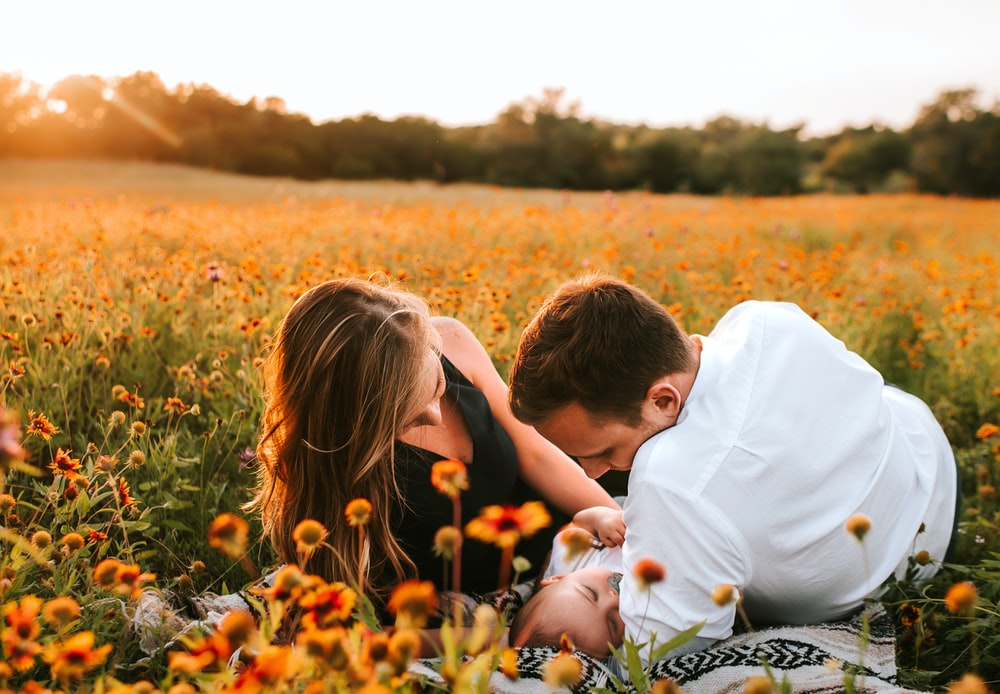family of three lying on bed of flowers