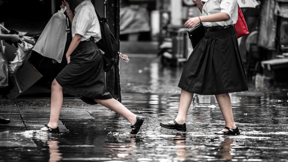 two women walking on wet ground