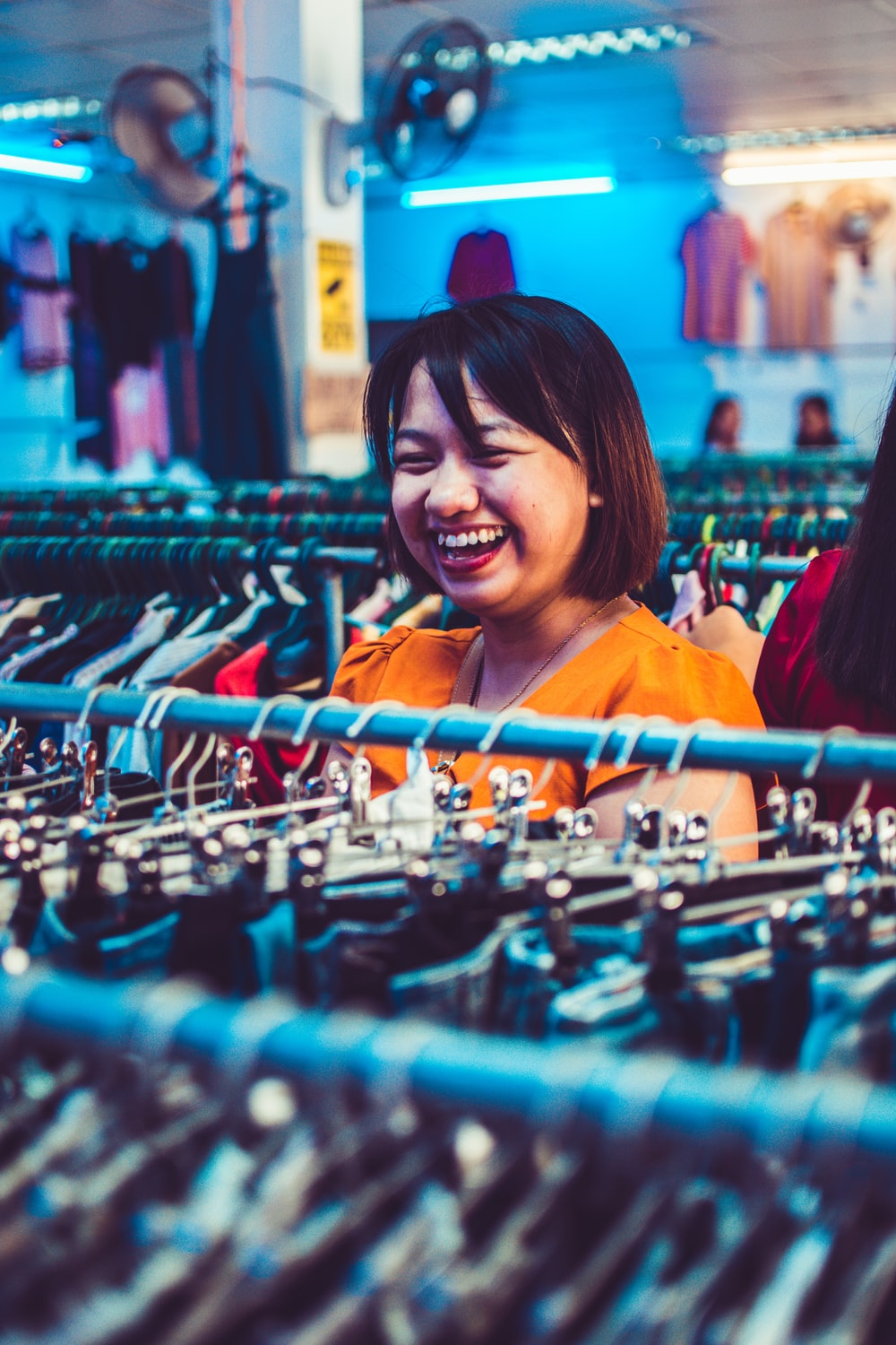 woman smiling standing beside clothes
