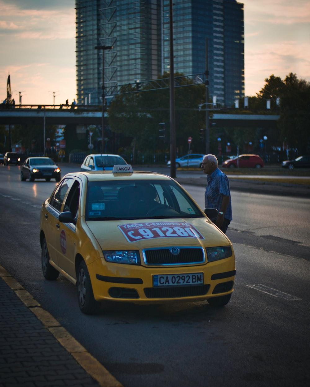 man standing beside taxi