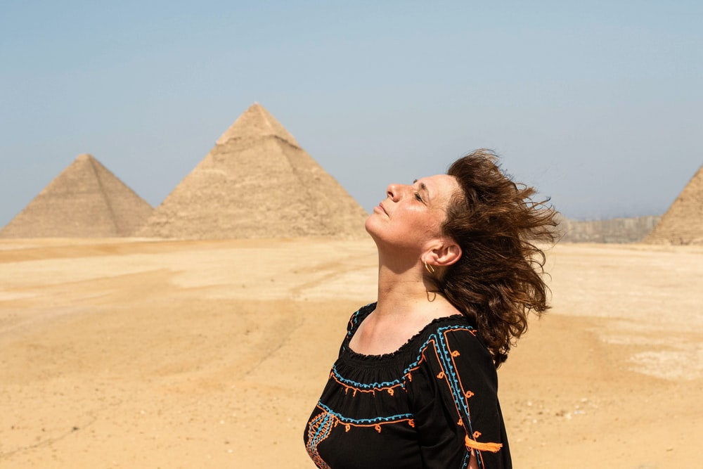 woman in black and blue crew-neck shirt near pyramids