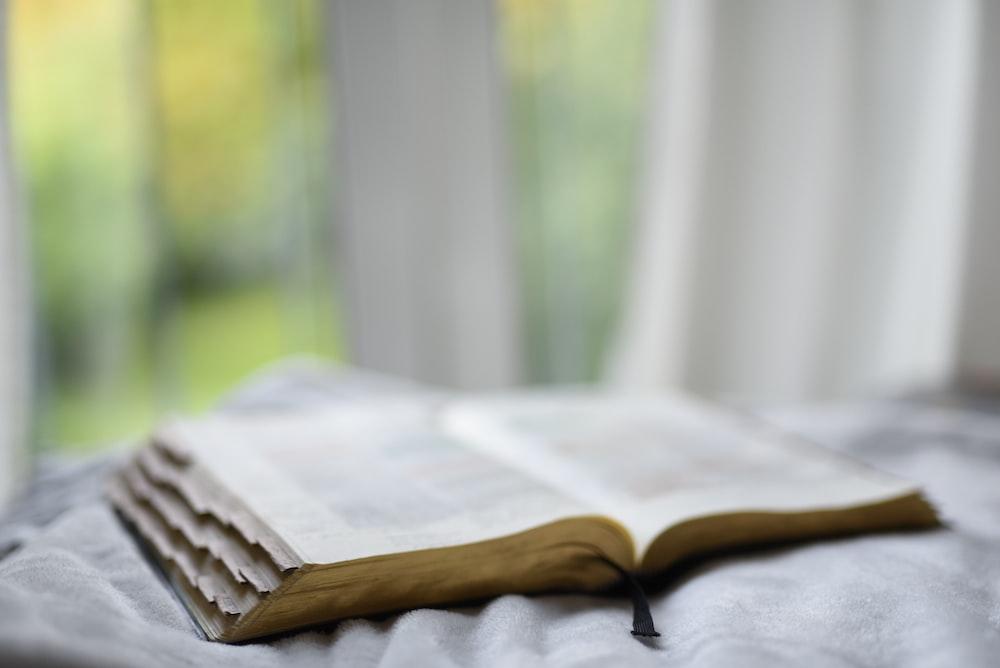 open book on gray textile