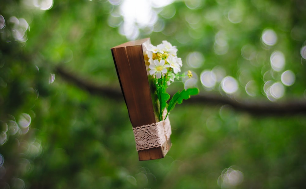 white flowers bounded on brown book