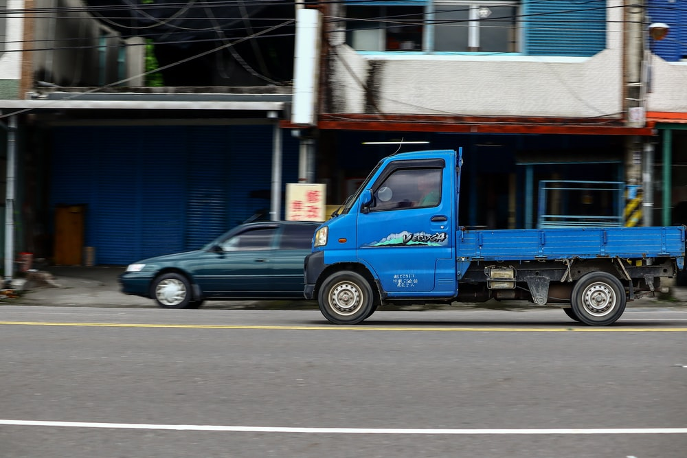blue vehicle on paved road