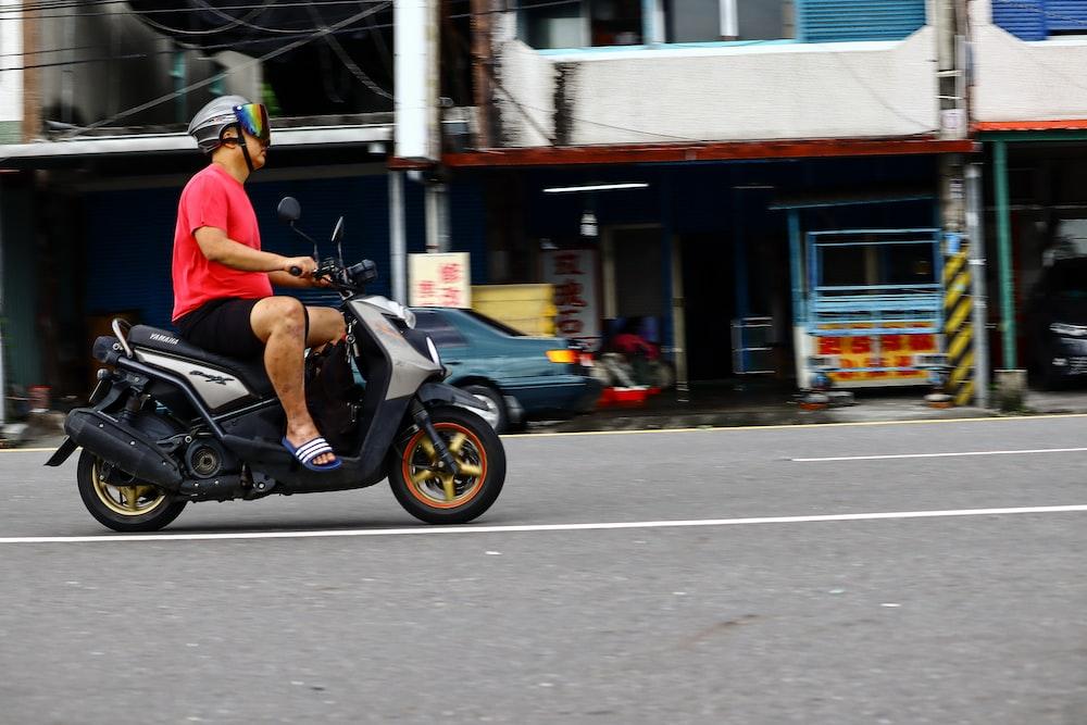 man wearing red shirt riding on motor scooter