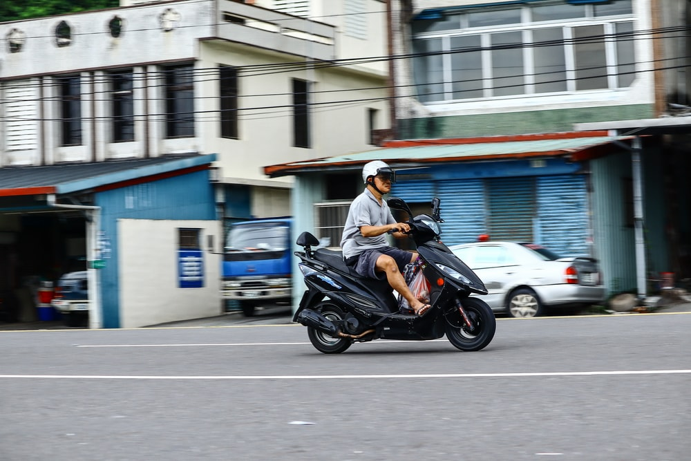 man riding motor scooter on road near cars and buildings