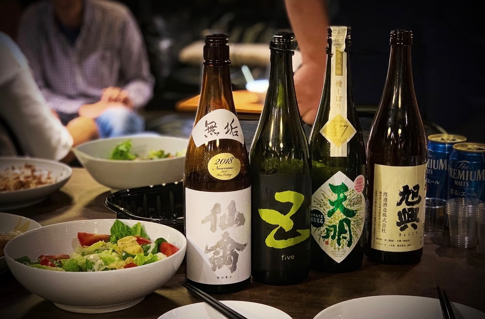 four assorted-labeled bottles beside bowls