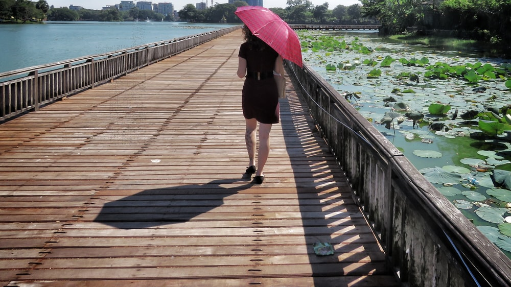 woman in black dress walking in wooden bridge