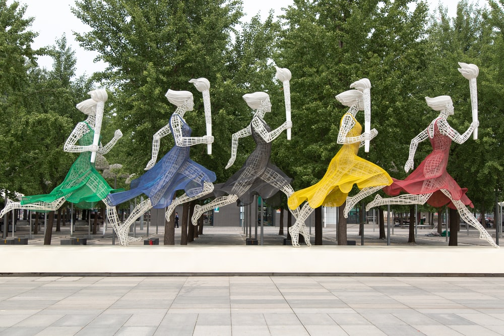 five running women wearing different dresses holding torch statue