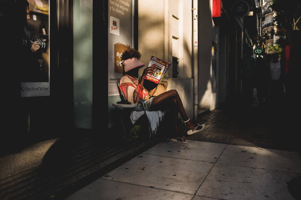 person sitting on chair holding book