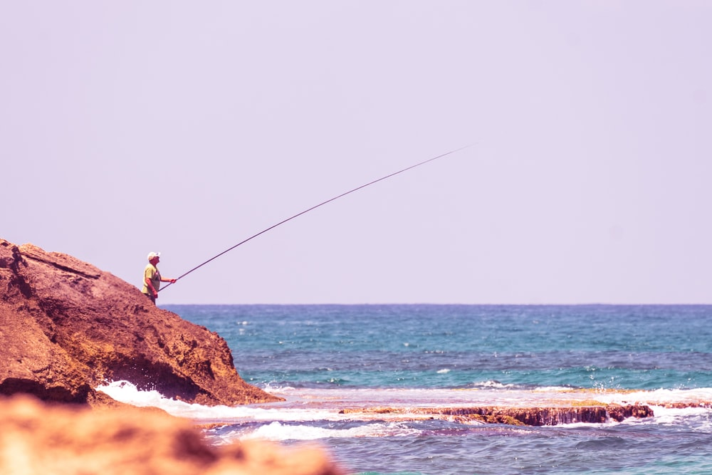 person fishing in body of water during daytime
