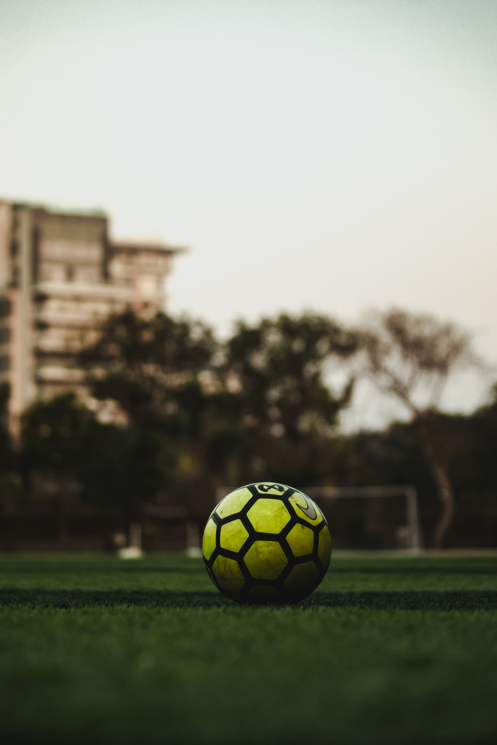 yellow and black soccer ball on field during daytime