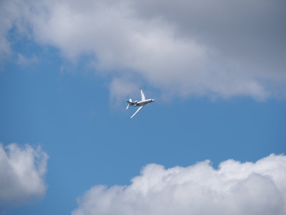 white airplane under blue and gray sky