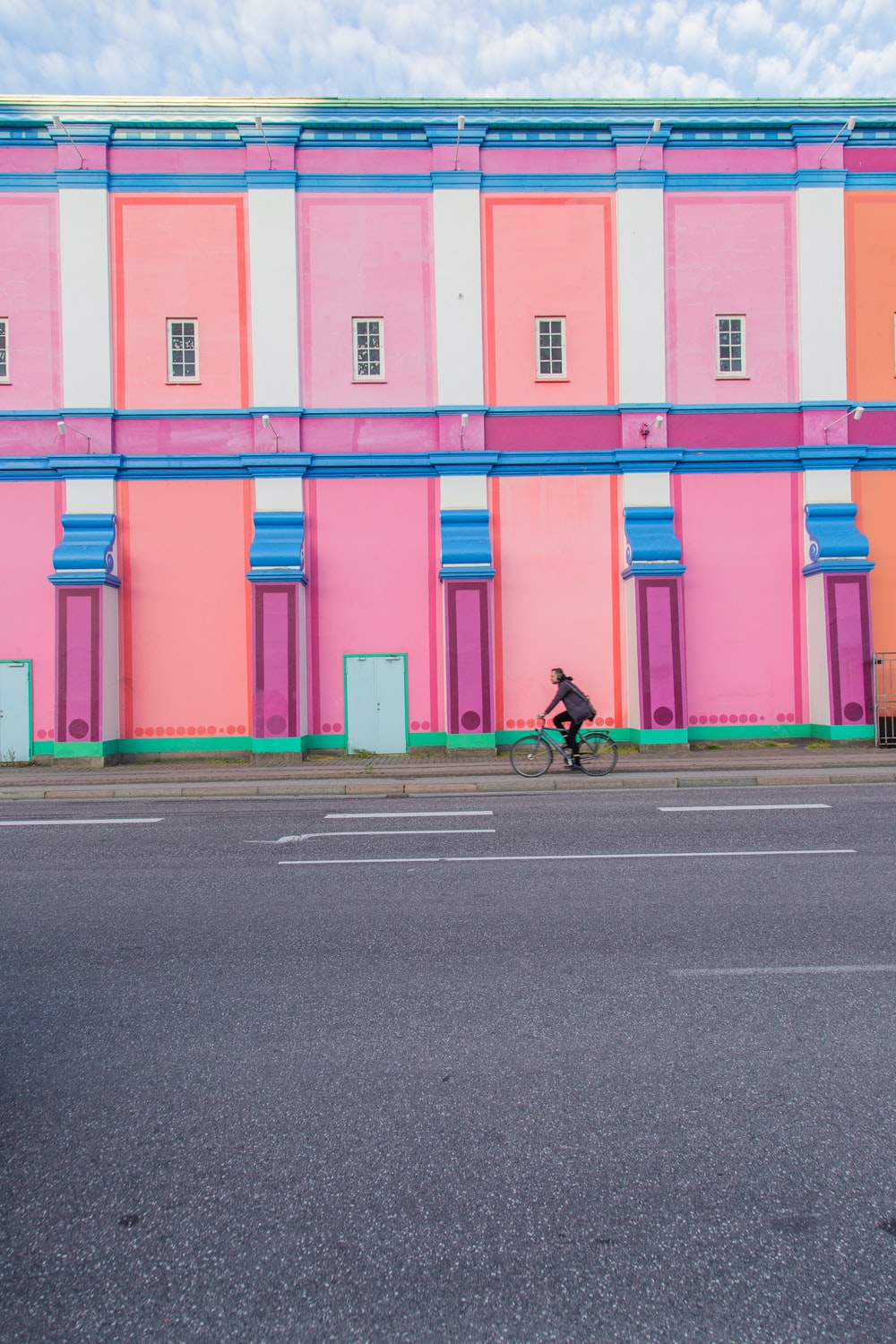 person driving a bike near multi-colored building during daytime