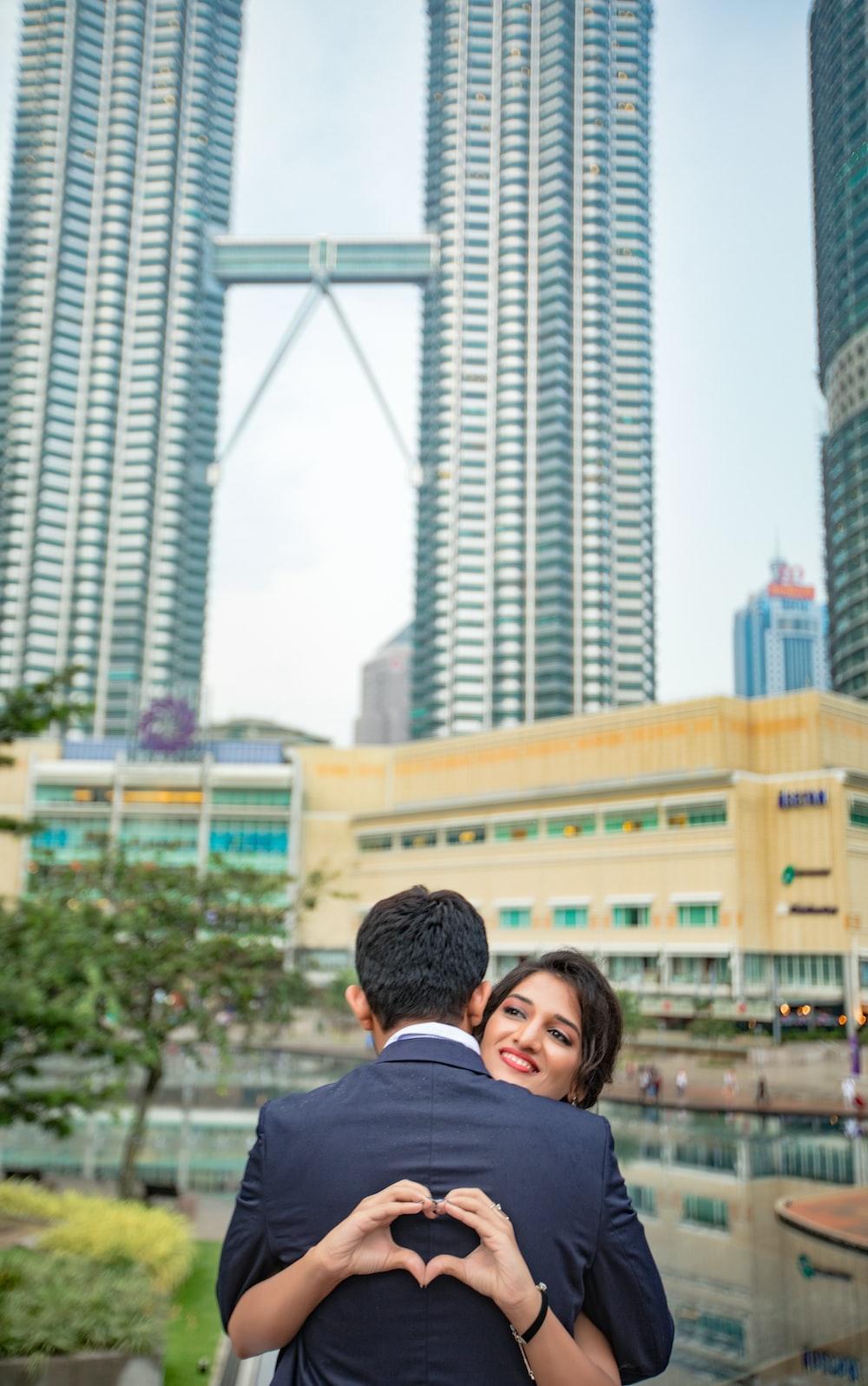 man hugging woman near Petronas Towers, Malaysia