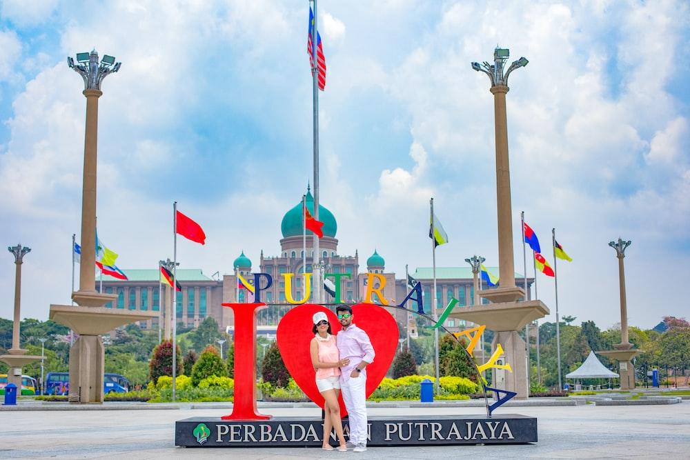 man and woman standing beside Putrajaya standee