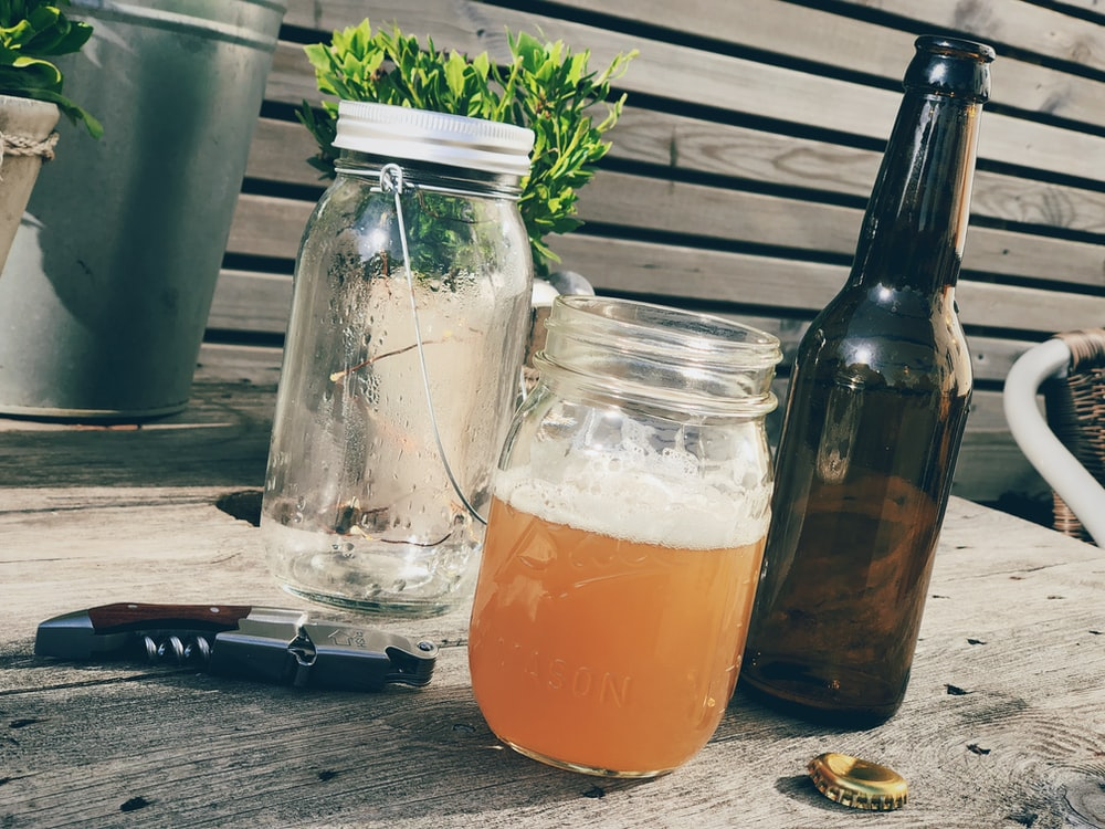 beer in clear glass mason jar on table
