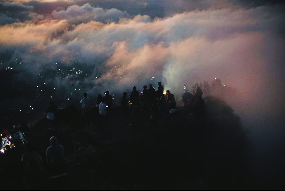 group pf people standing on cliff during fogs