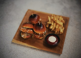 burgers and fries on brown wooden surface