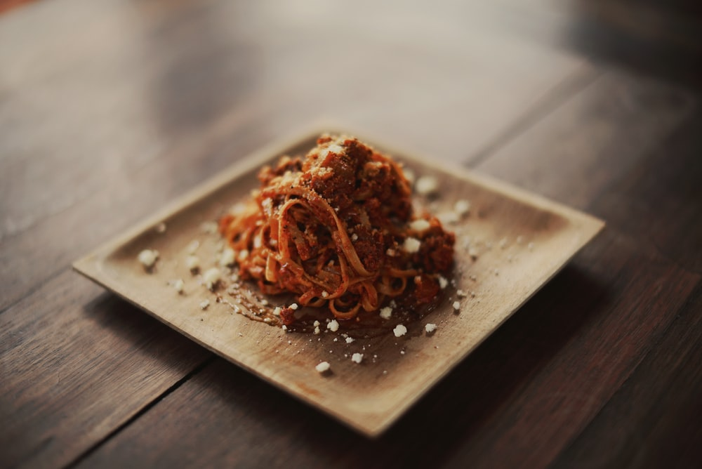spaghetti served on brown plate