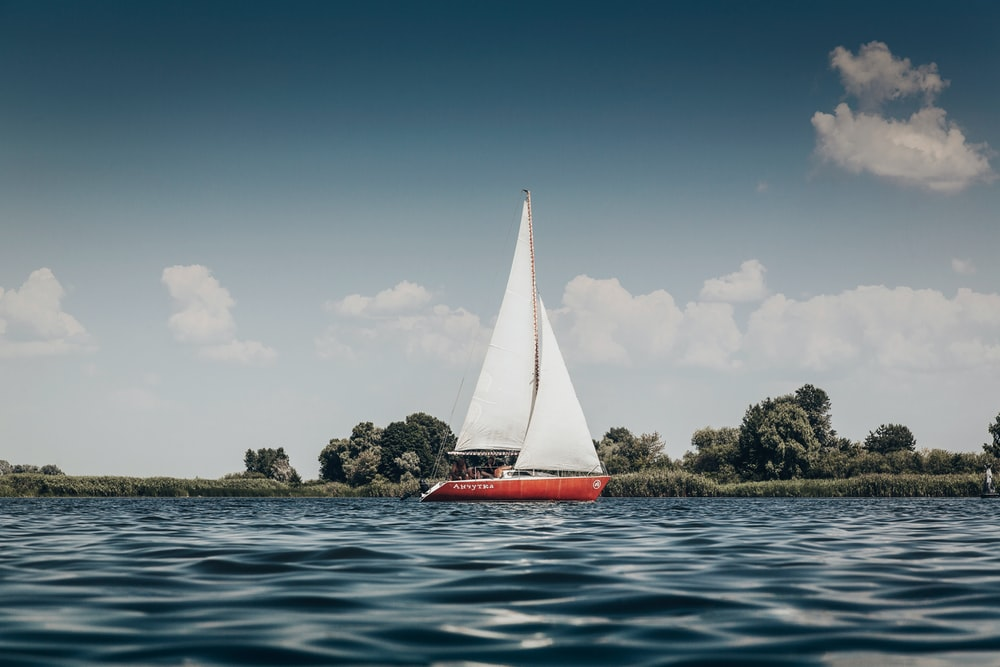 red sail boat on body of water during daytime