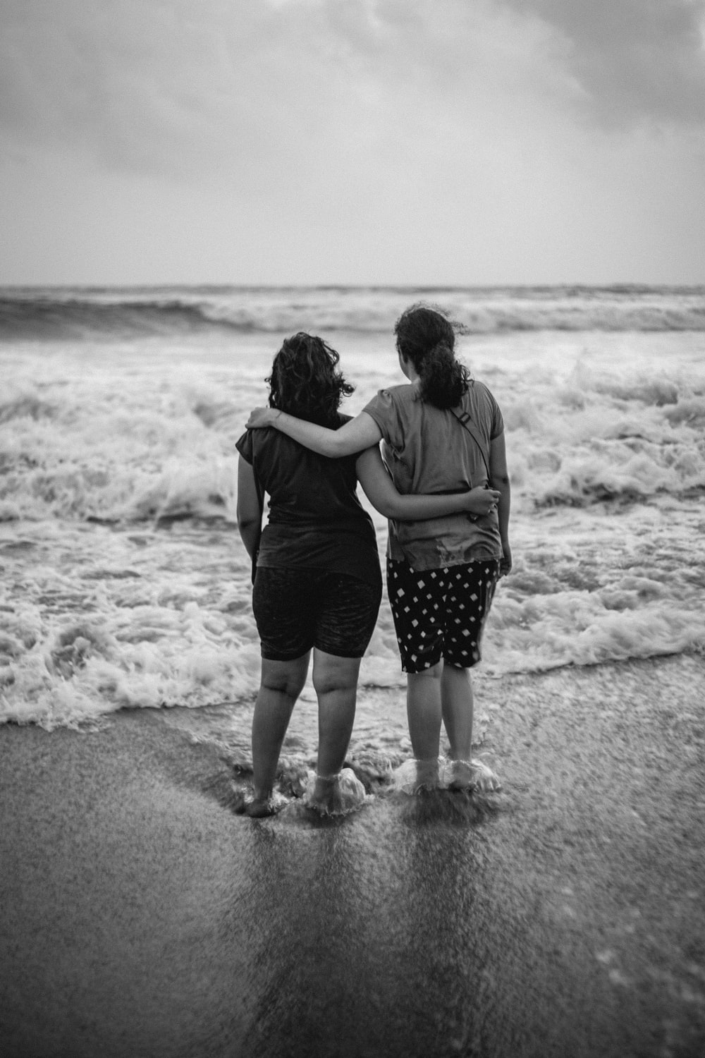 two women standing on beach line